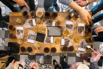 people tasting specialty coffee around a table